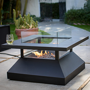 Walmart square black fire pit table holding a glass of wine with fire burning on a patio photo