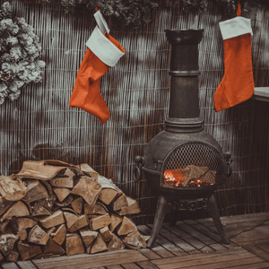 Two red and white stockings hanging next to a fireplace photo