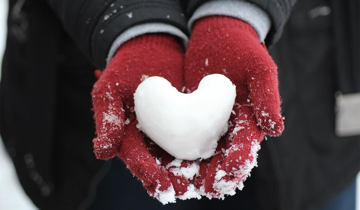 Red gloves holding a snowball shaped like a heart