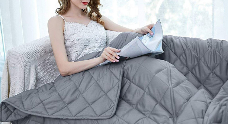 Women on a couch with a gray weighted blanket from Amazon photo