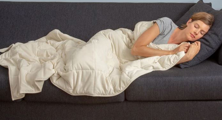 Woman sleeping on a couch with a white blanket from Target photo
