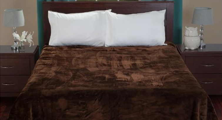 Bed with white pillows and a brown weighted blanket from Overstock photo