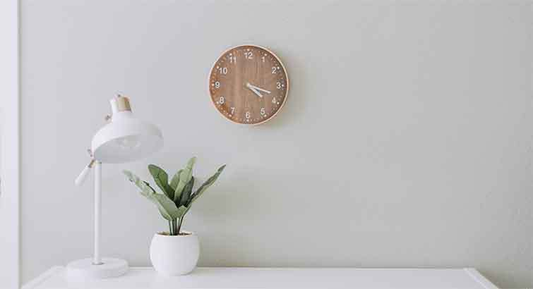white desk with a white desk lamp, potted plant in a white pot, and a wooden clock on the wall
