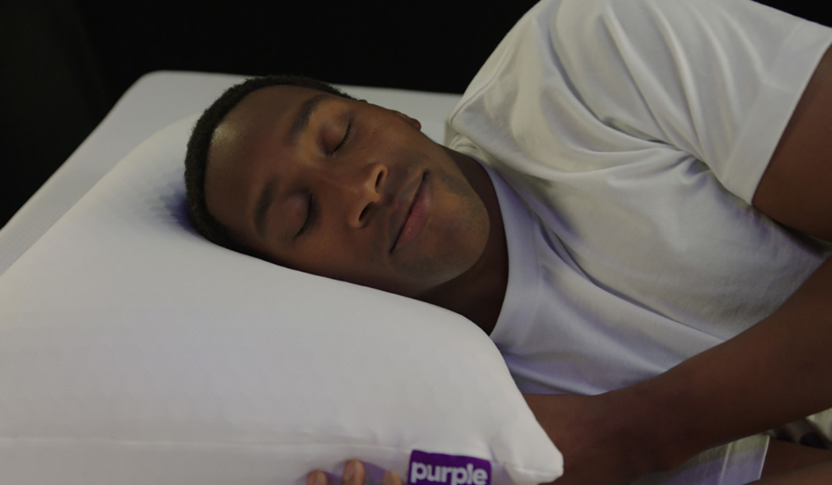 A man sleeps on the Purple Harmony Pillow photo