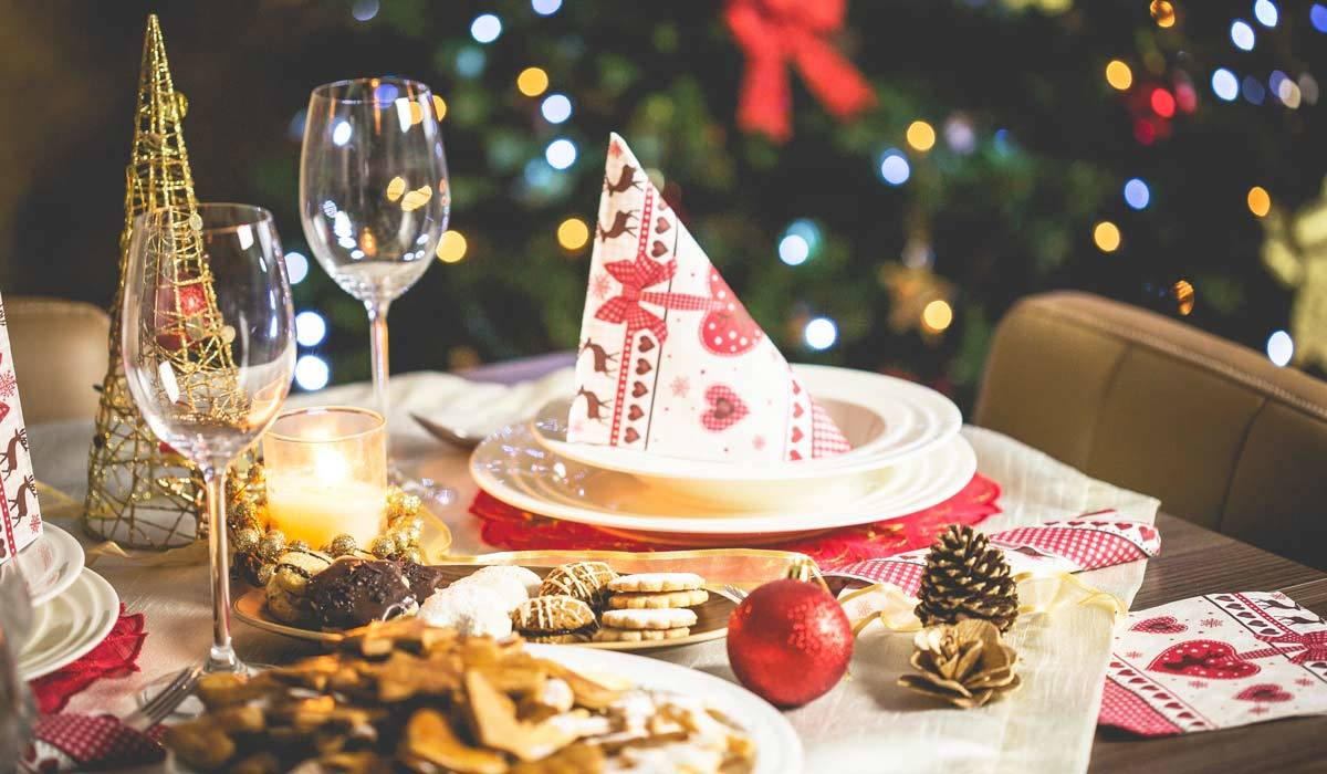 Christmas table setting featuring plates, cookies, wine glasses, and decorative accents photo