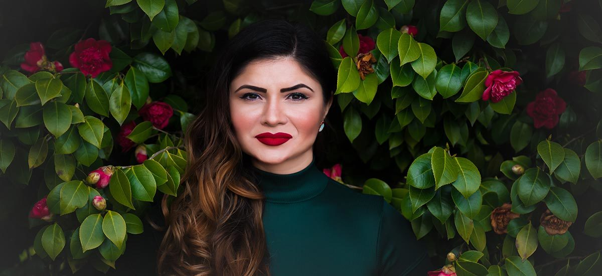 A woman wears a green turtleneck and red lipstick in front of a rose bush