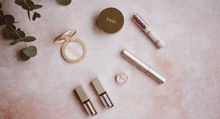 Various makeup products against a pink background