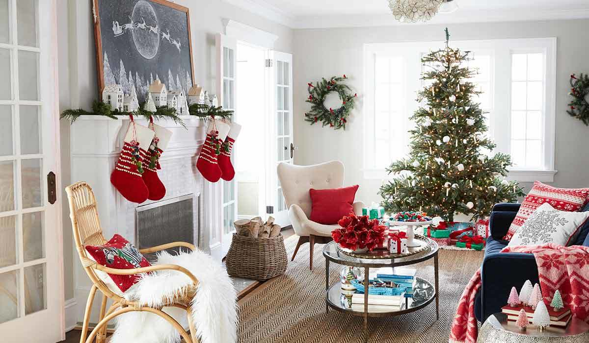 White living room with a fireplace, stockings, Christmas tree, and presents photo