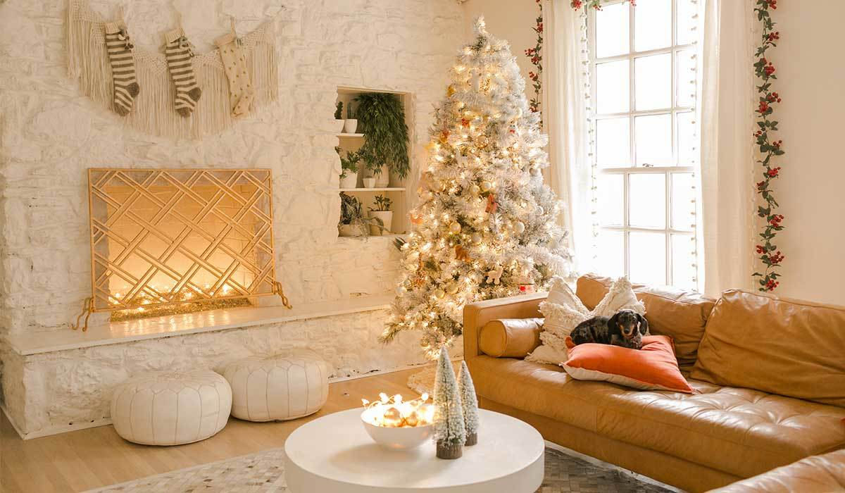 White and tan living room with white Christmas tree and fireplace photo