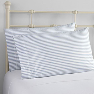White and blue striped pillows on a white bed photo