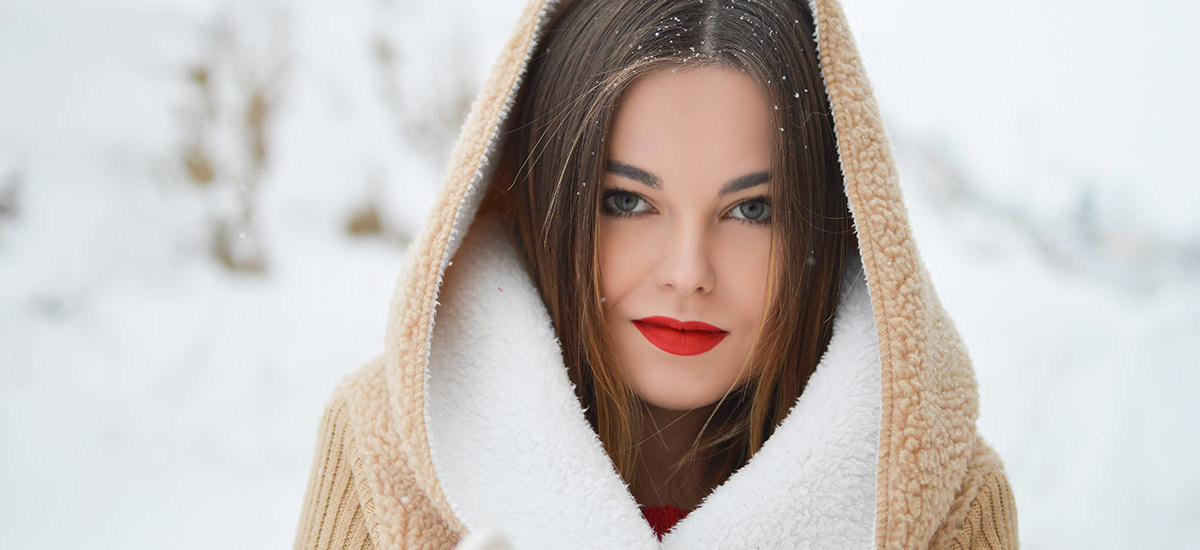 A woman stands outside wearing a sherpa hood and red lipstick