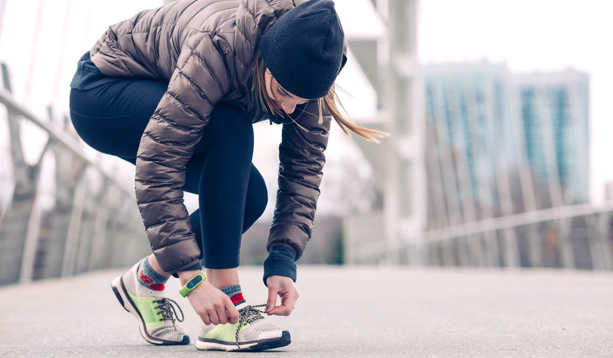 Women tying her shoes on a run on a bridge
