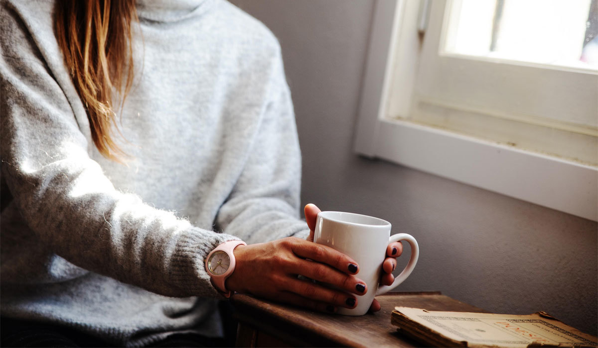 woman in a gray turtleneck sweater holding a mug
