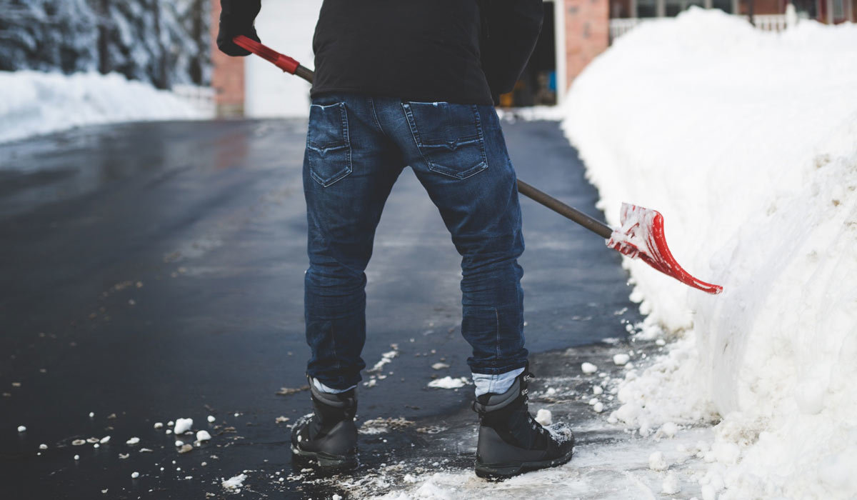A man shoveling snow with a red shovel