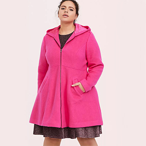 Woman wearing a dress and a neon pink hooded coat from Torrid photo