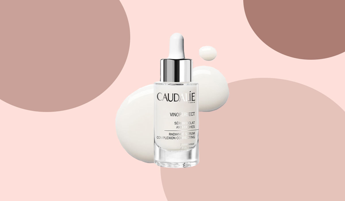 Caudalíe facial serum in bottle in front of pink and dotted background.