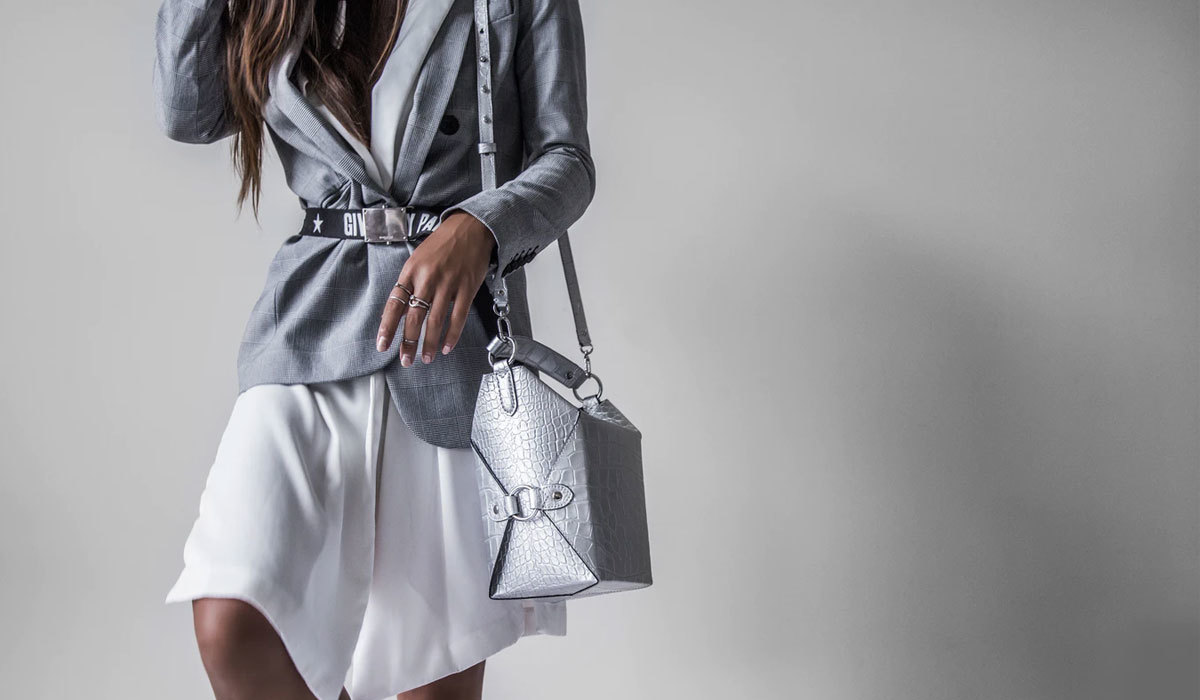 Woman in cool toned apparel with a silver chrome crocodile handbag slung across her shoulder.