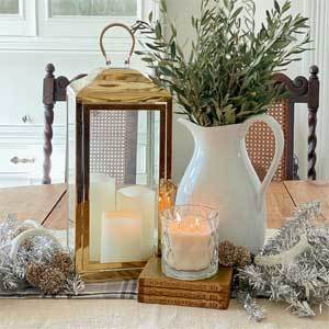 White pitcher filled with greenery with candles and gold lantern. photo