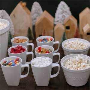 Mugs filled with candy and bowls of popcorn. photo