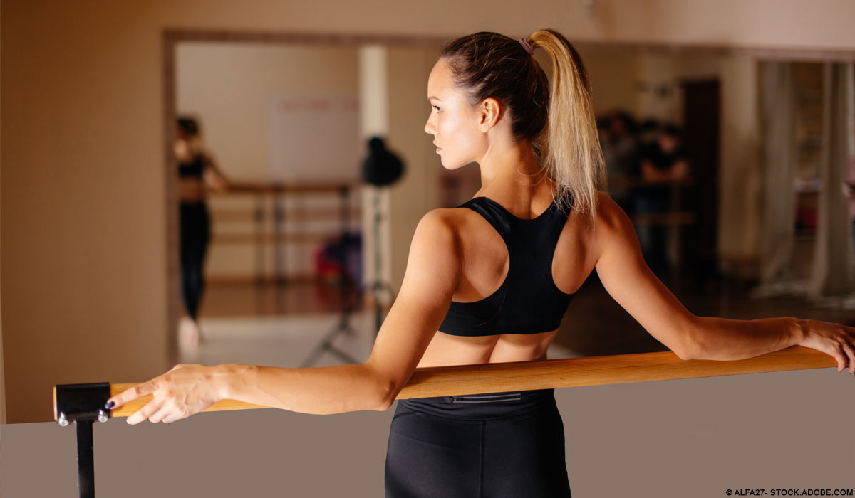 Woman in leggings and sports bra holding plank position