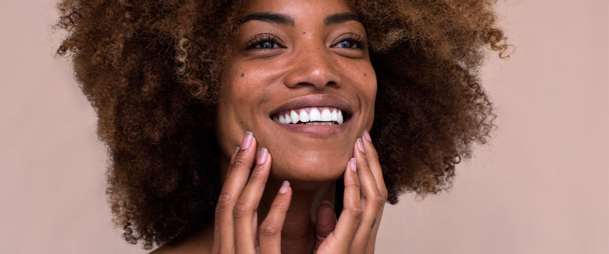 A woman with healthy skin touching her face photo