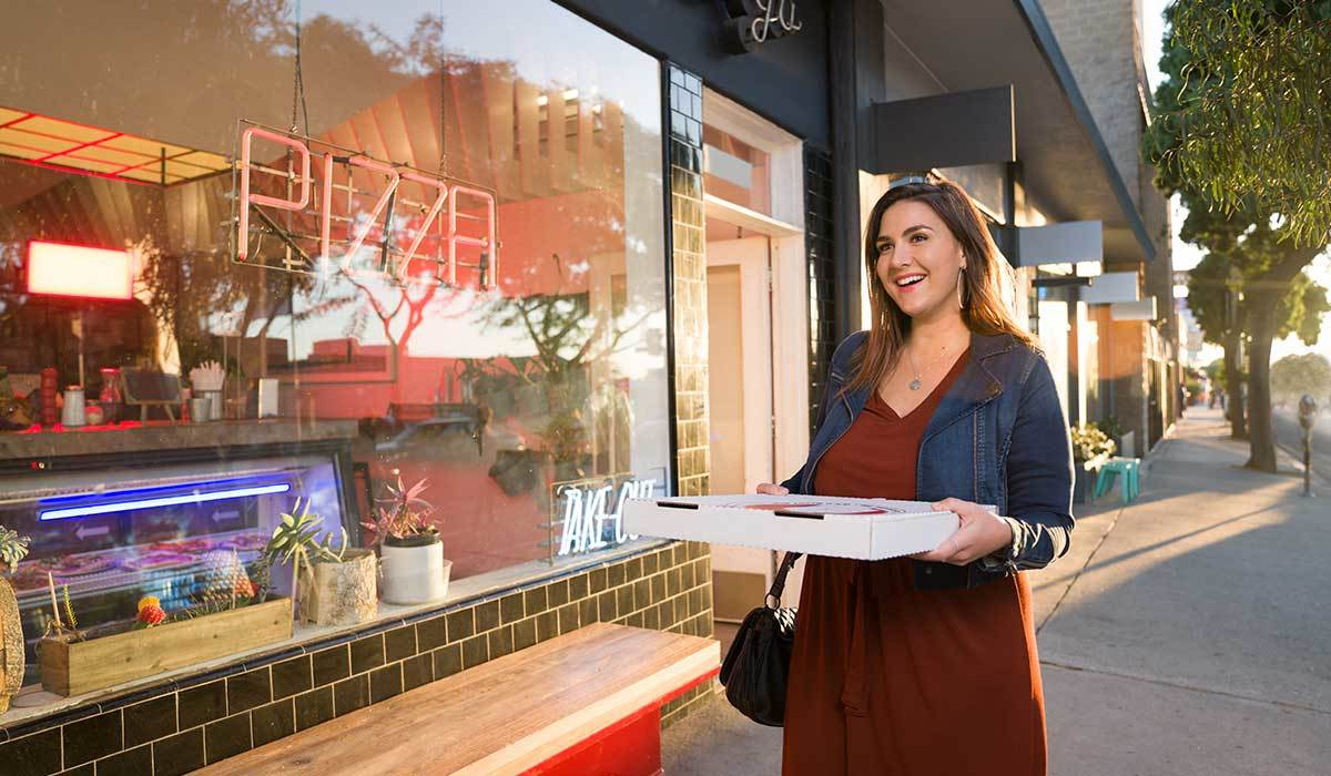 Women smiling walking and carrying a pizza outside a shop photo
