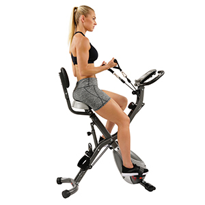 A woman uses a Sunny Health & Fitness folding exercise bike from Walmart photo
