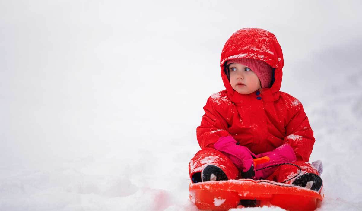 toddler in the snow wearing a red snowsuit on a sled
