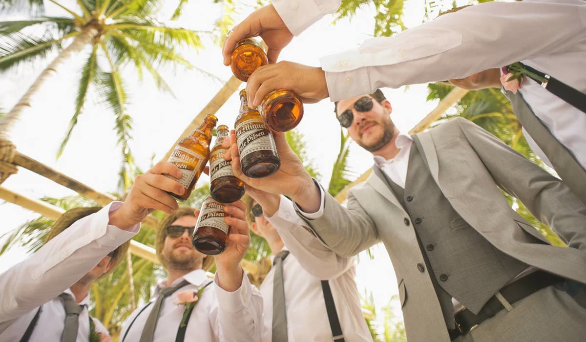 A groom and his groomsmen clinking beer bottles under palm trees