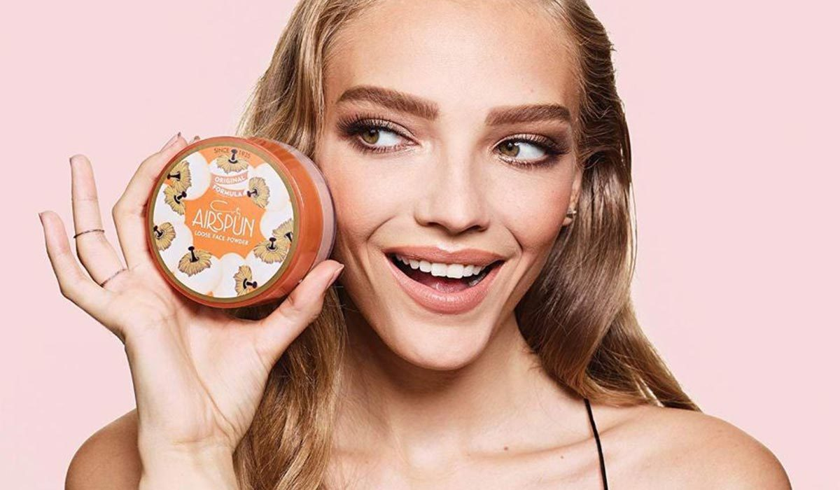 Woman holding a jar of Coty loose face powder from Amazon photo