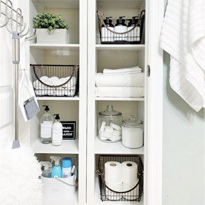 Bathroom closed with baskets and clear glass containers. photo