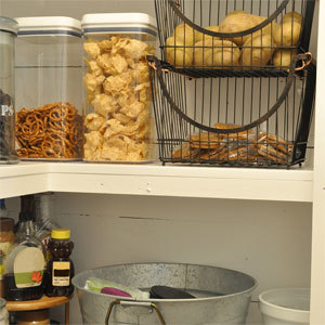 Kitchen pantry with wire baskets and clear food containers. photo