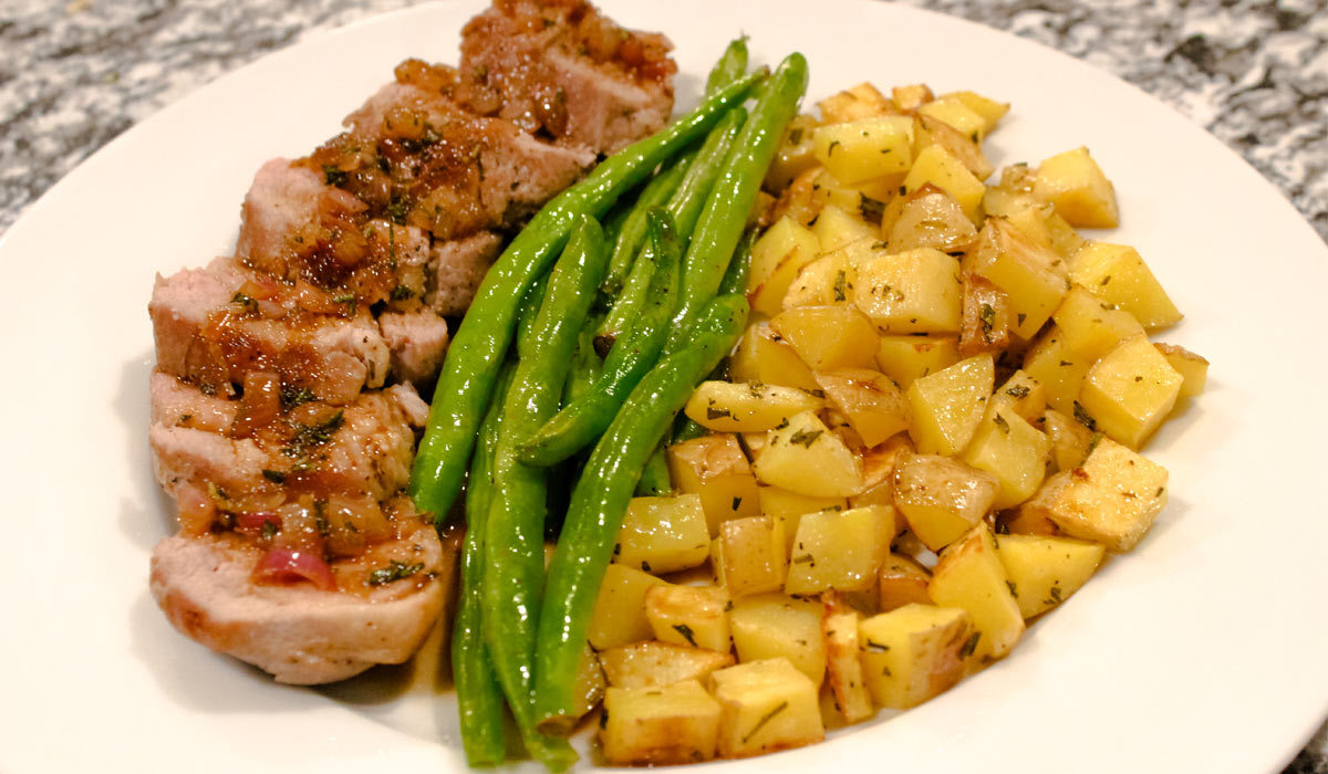 Pork, diced potatoes, and green beans on plate. photo