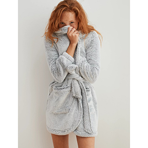 A woman wears a gray Fuzzy Sherpa Robe from Aerie photo