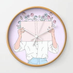 Wall clock with artistic print featuring a woman reading a book from Society 6 photo