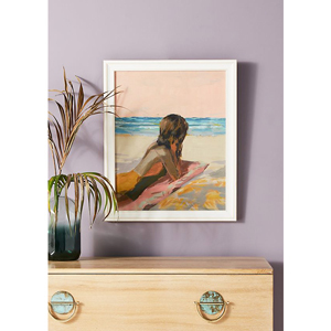 Framed wall print with girl laying on a surfboard on the beach from Anthropologie photo