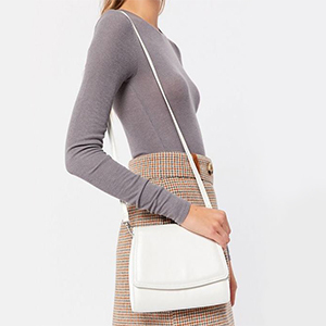 Woman holding a white crossbody bag from Urban Outfitters photo