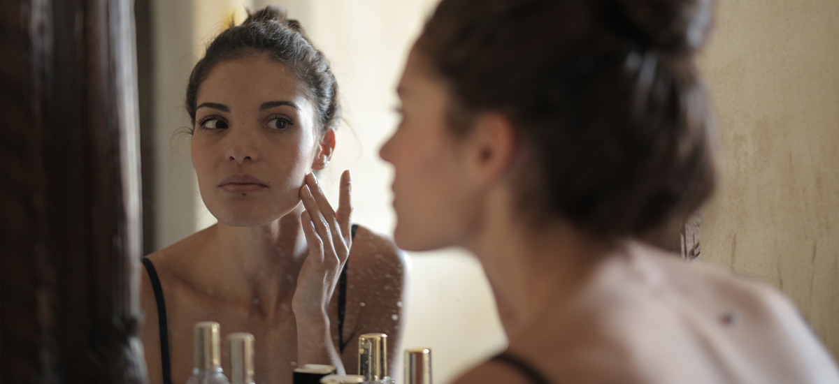 A woman touches her face in front of a mirror