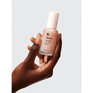 A woman holds a light pink bottle of Glossier Futuredew photo