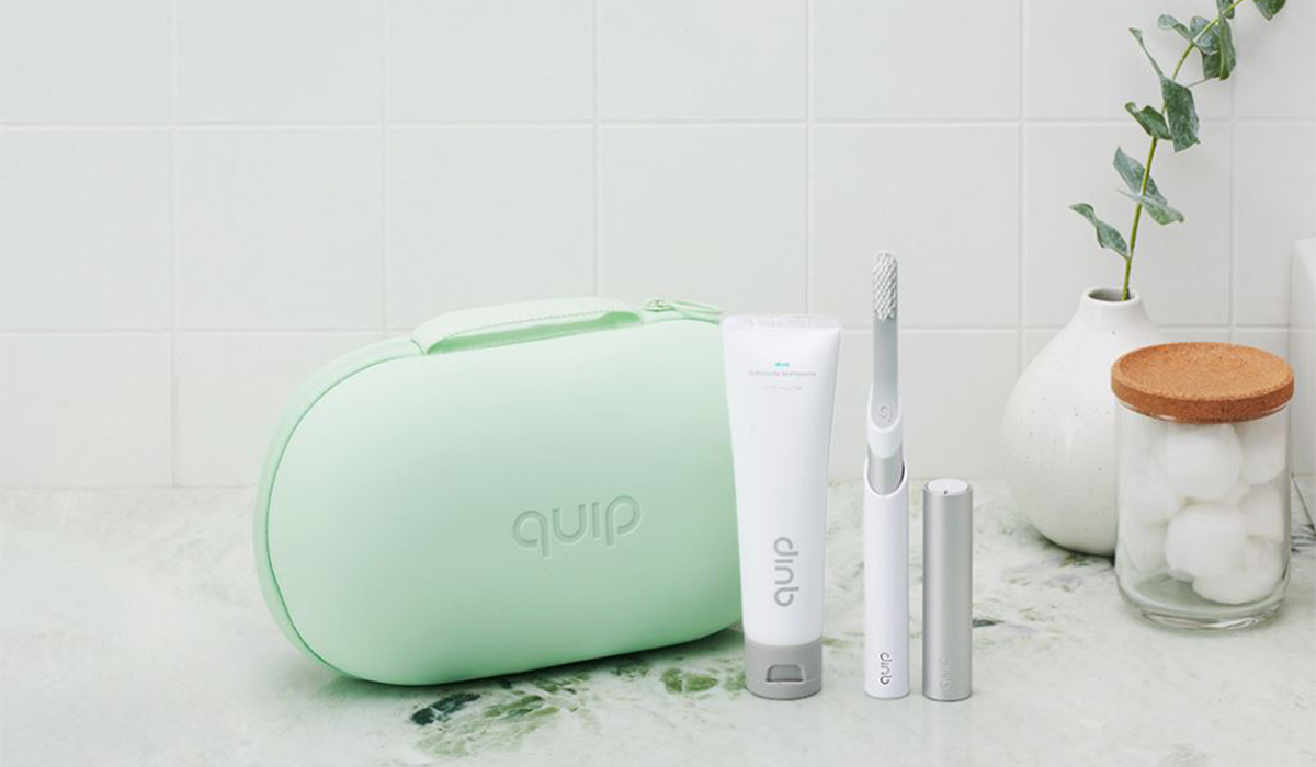 Mint green case with a Quip toothbrush, tooth paste, and floss photo