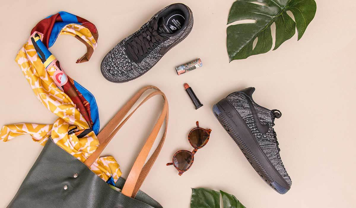 A flat lay of a purse, lipstick, pair of sunglasses, and sneakers