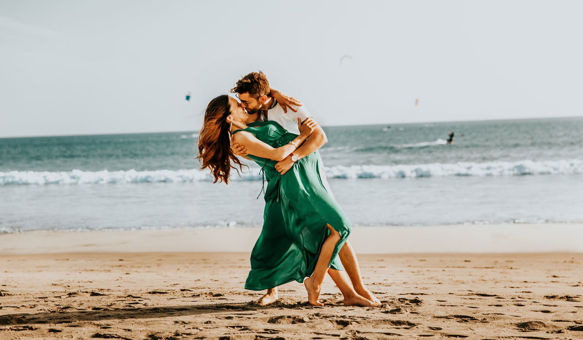 Pregnant couple kissing on the beach