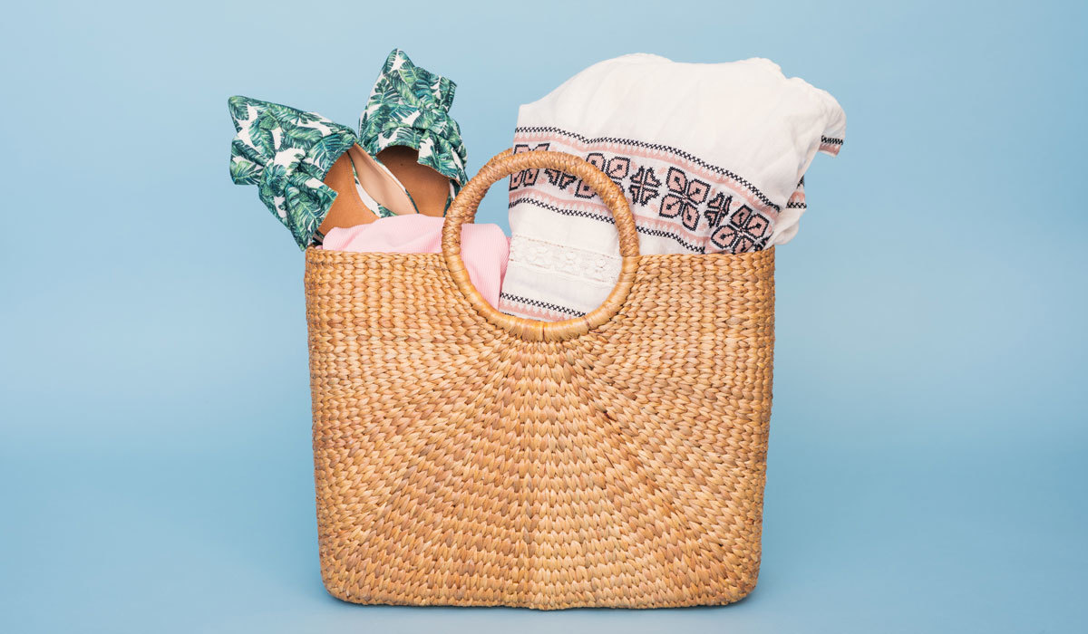 Straw beach bag with a towel and shoes tucked inside