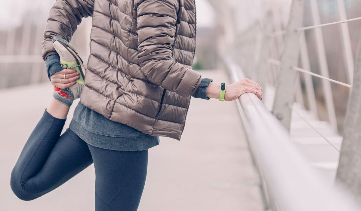 A woman wearing a lightweight jacket and running shoes