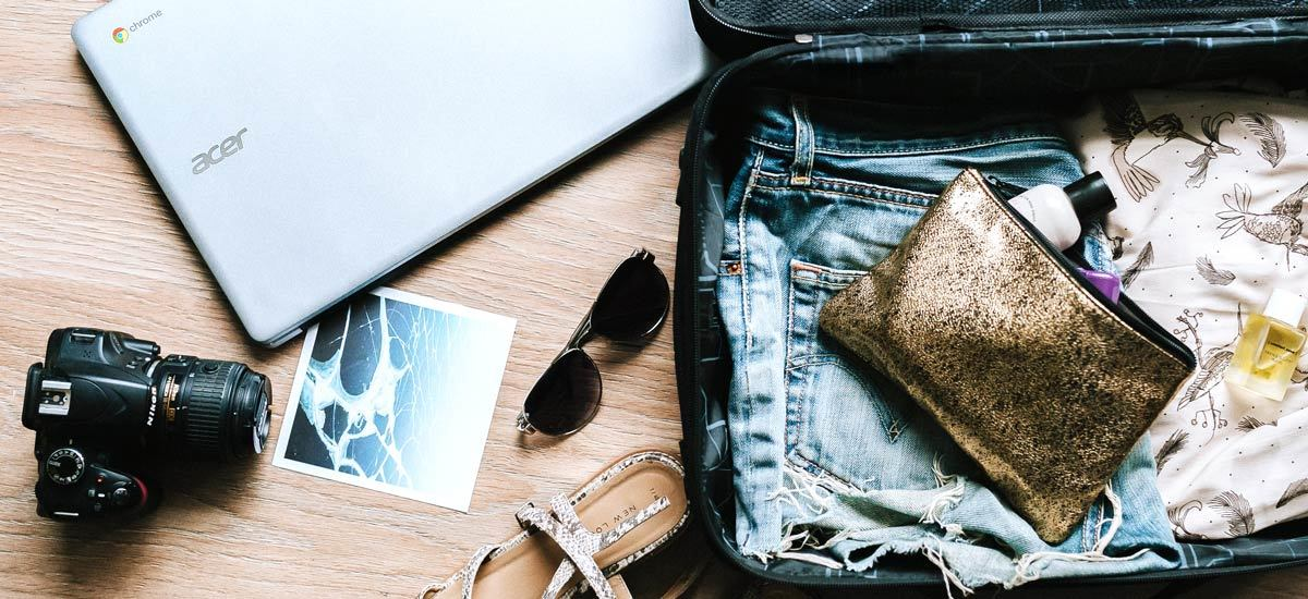 Camera, laptop, and suitcase full of clothes and accessories