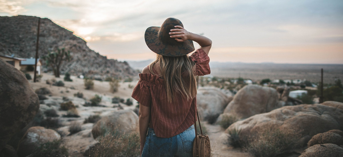 Woman wearing a hat, top, and jeans while standing in a desert