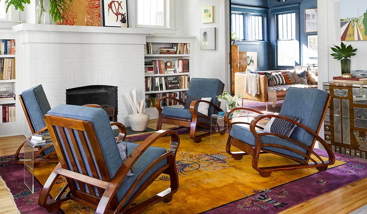 Remodeled living room with blue lounge chairs and a large area rug photo