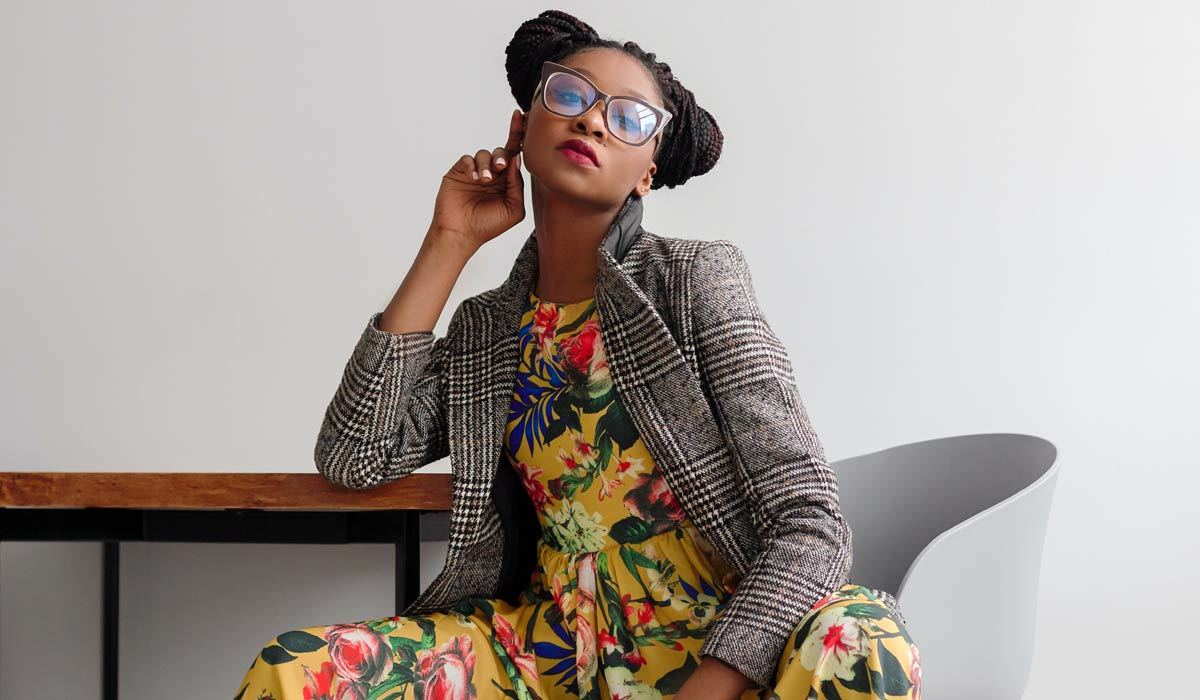 A woman wearing a blazer and floral dress