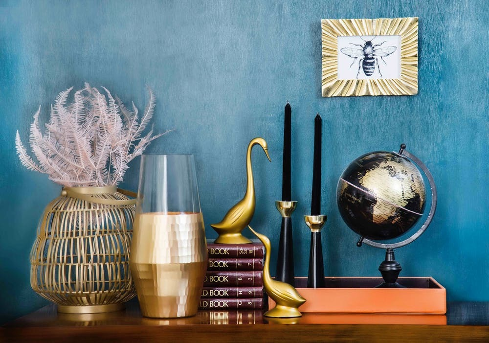 Table with vases, books, candles and a globe