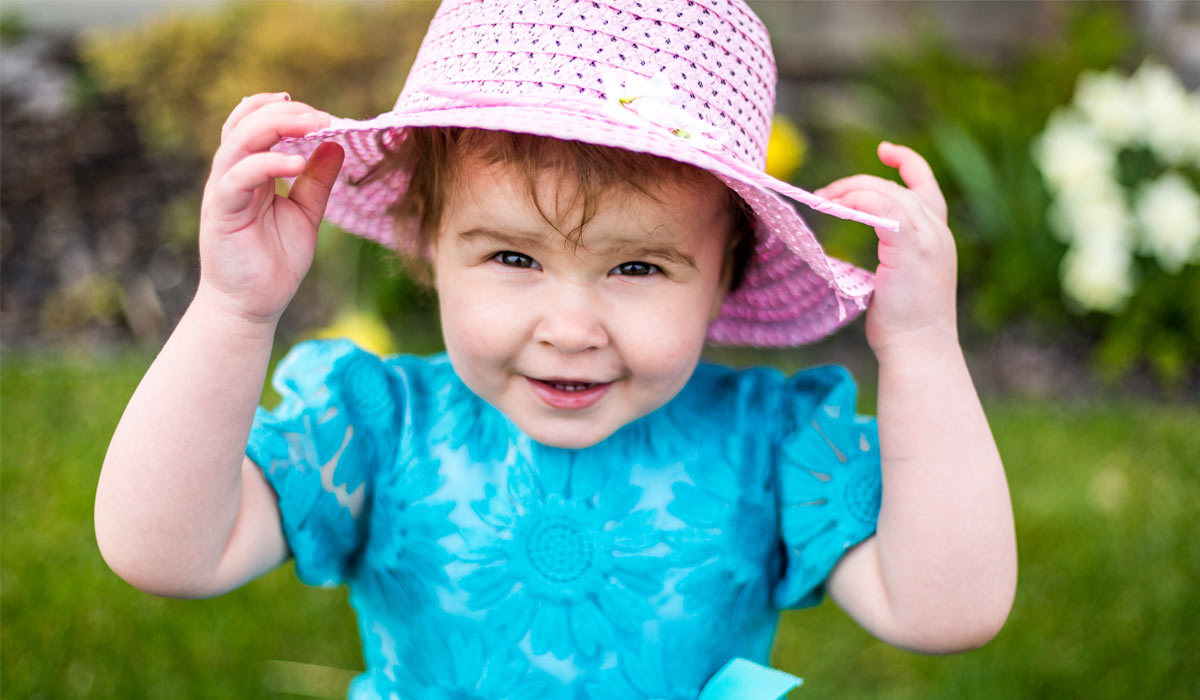 Little girl wearing a pink sun hat and blue dress outside